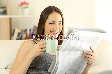 happy female reading a newspaper on