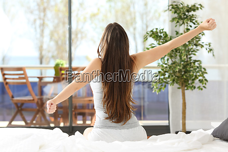 woman stretching arms and waking up