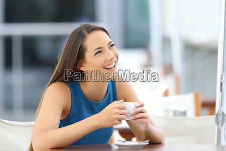 woman daydreaming in a coffee shop
