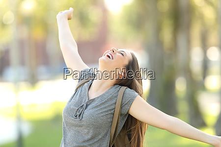 joyful girl raising arms in the