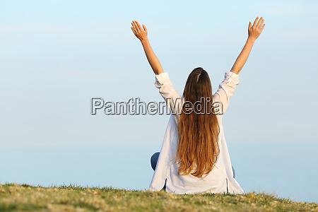 satisfied woman raising arms watching sky
