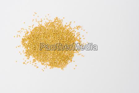 yellow mustard seeds on white