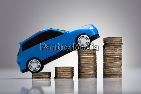 car over rising stacked coins