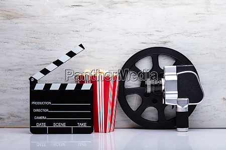 movie camera with popcorn and clapper