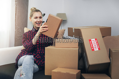excited woman opening boxes after home