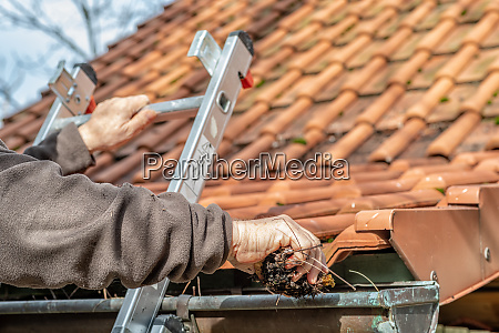 man on a ladder cleaning house