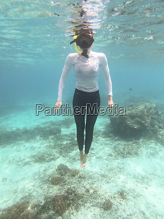 woman with mask snorkeling in blue