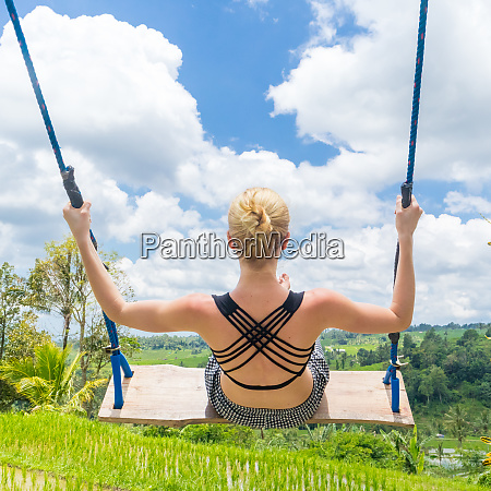 happy female traveller swinging on wooden