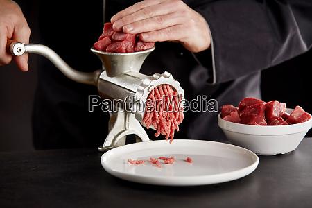 cook in black uniform mincing meat