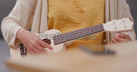 woman practice ukulele