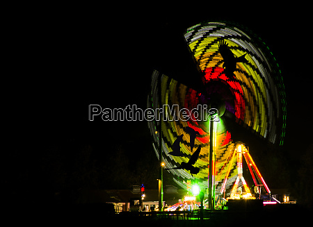 colorful carousel by night with silhouette