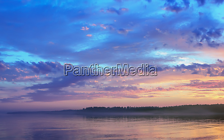 amazing sunset over the forested shore