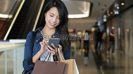 shopping woman using cellphone and holding