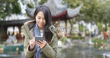 young woman using mobile phone sending