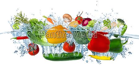 fresh vegetables splashing into blue clear
