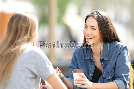 two friends talking drinking coffee in