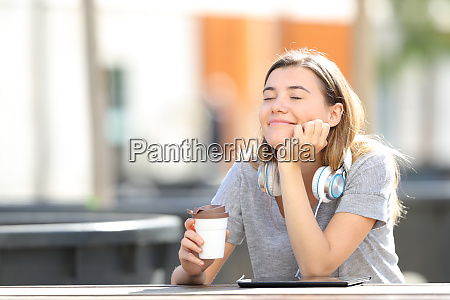 happy girl resting holding coffee in