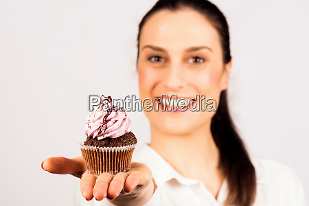woman presenting sweet cupcake
