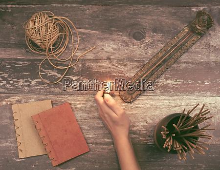 woman hand lights a incense stick