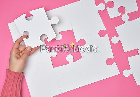 female hand puts white big puzzles