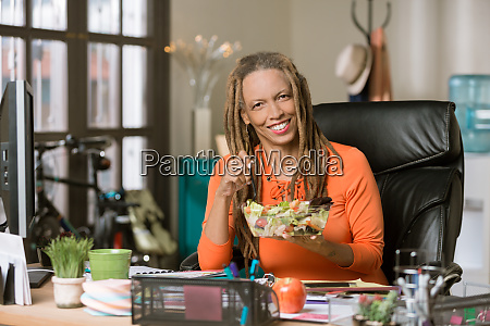 stylish woman with drealocks eating a