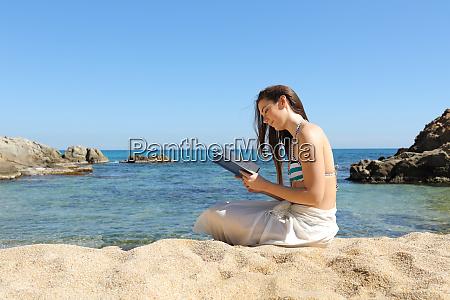 tourist on the beach reading a