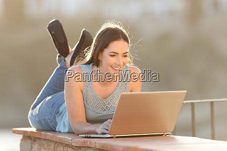 happy woman using a laptop lying