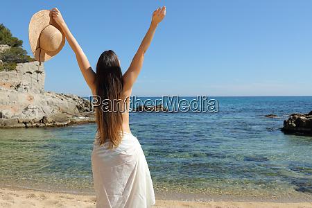 happy tourist raising arms celebrating beach