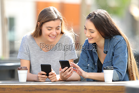 two friends comparing their smart phones