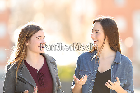 two young women walking and talking
