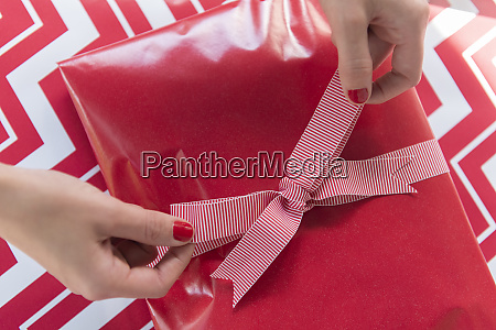 hands of woman tying bow on