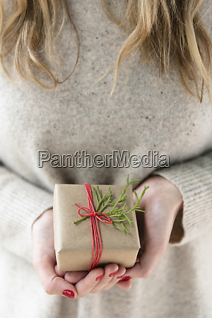 hands of woman holding christmas present
