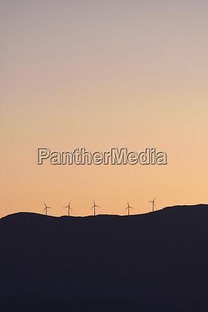 silhouette of wind turbines on hill