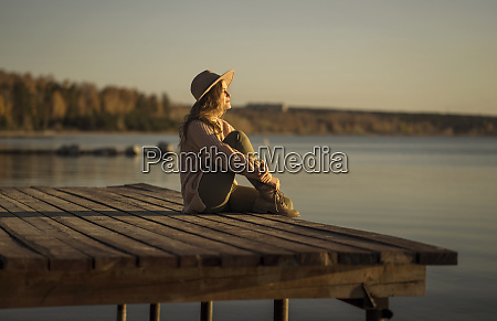 young woman sitting on wooden pier