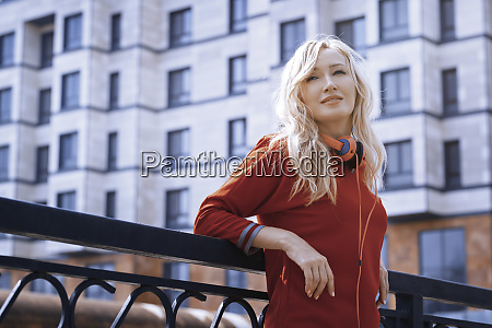 woman with headphones leaning on railing