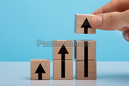 persons hand holding arrow sign wooden
