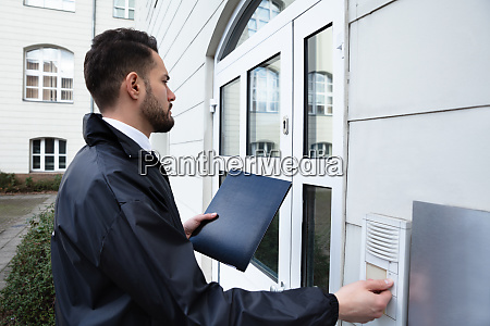 man pressing the door bell