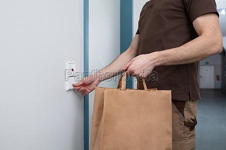 man ringing the door bell holding