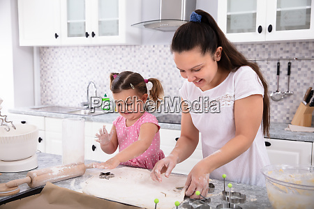 mother and daughter making cookies with