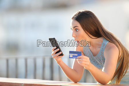 amazed online buyer holding credit card