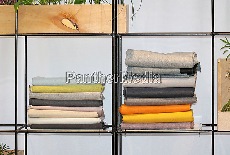 wool sweaters on metal shelf