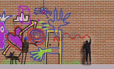 man spraying graffiti on brick wall