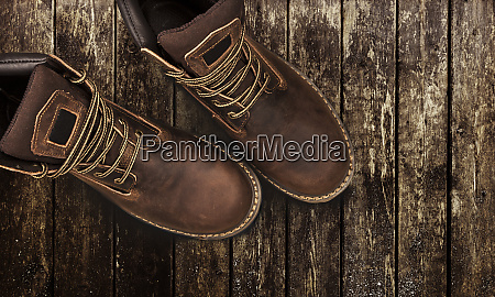 brown mens boots on a wooden