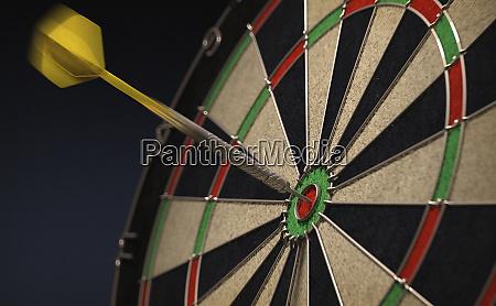 dart hitting bulls eye on dartboard