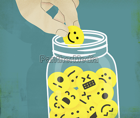 hand choosing smiley face from jar
