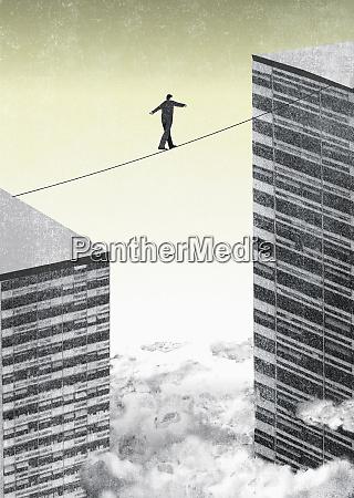 businessman walking tightrope between two office