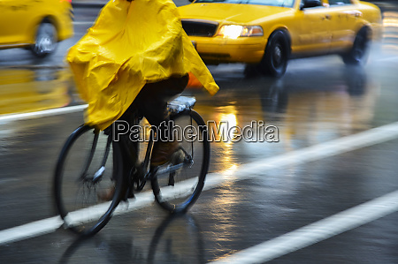 cyclist in yellow poncho during rain