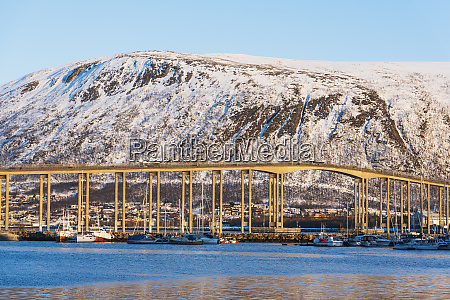 bridge by snow covered hill in