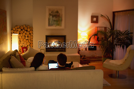 couple using digital tablet on living