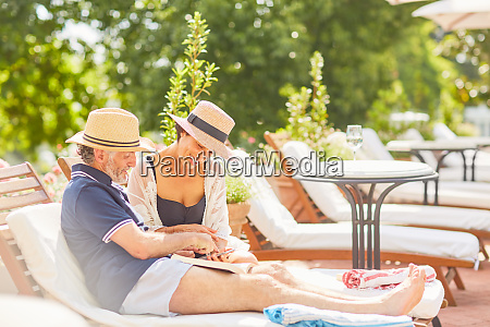 couple relaxing reading book and using